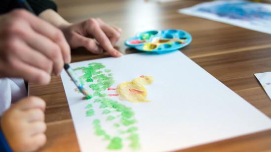 Malende Kinderhände mit Papier und Pinsel